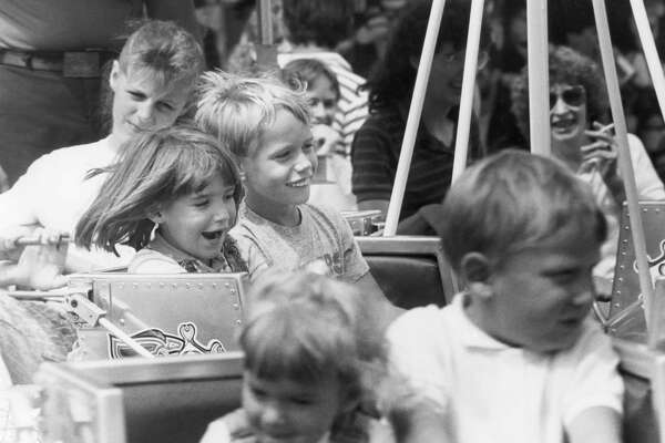 Amber Mapes, 5, and brother Paul Mapes, 7, enjoy a ride on the midway. August 1989