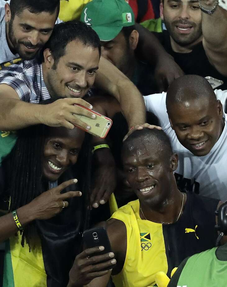 Jamaica's Usain Bolt takes selfies with fans after winning the gold medal of the men's 100-meter final during the athletics competitions of the 2016 Summer Olympics at the Olympic stadium in Rio de Janeiro, Brazil, Sunday, Aug. 14, 2016. (AP Photo/Matt Dunham) Photo: Matt Dunham, Associated Press