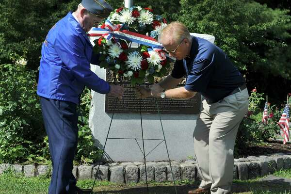 John Edmond, left, 90, of Danbury, who served on the U.S. Providence during World War II and Mayor Mark Boughton,  place a wreath at the War War II monument Monday morning. A ceremony at the Rogers Park Rose Garden marked the 71 st anniversary of the Japanese surrender and the end of World War II,  Monday, August 15, 2016 in Danbury.