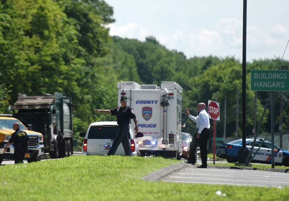 Westchester County Police officers monitor the scene where a suspect's car crashed at Westchester County Airport in White Plains, N.Y. after reports of shots fired in north-western Greenwich. Photo: Tyler Sizemore / Hearst Connecticut Media / Greenwich Time