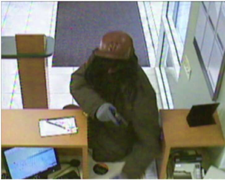 """The """"Dreaded Bandit"""" is seen on a security camera jumping the counter of a Bay Area bank."""
