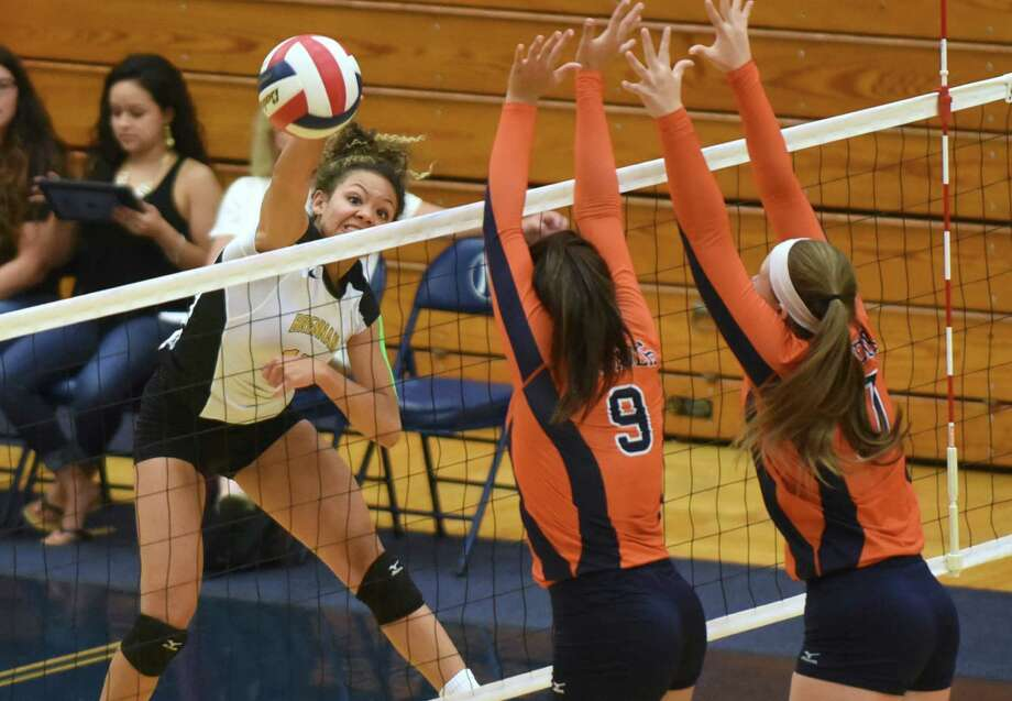 Kylexus Block of Brennan tips the ball as Lauren Martinez (9) and Emily DeWalt of Brandeis defend during District 27-6A high school volleyball action at Taylor Field House on Sept. 23, 2015. Photo: Billy Calzada /San Antonio Express-News / San Antonio Express-News