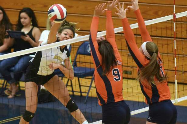 Kylexus Block of Brennan tips the ball as Lauren Martinez (9) and Emily DeWalt of Brandeis defend during District 27-6A high school volleyball action at Taylor Field House on Sept. 23, 2015.