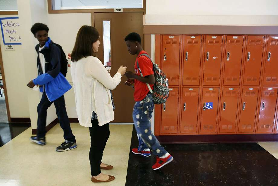 Eighth-grade math teacher Tina Hu hands out passes to students Damarion Travis (left) and Damani William on the first day of school at S.F.'s Martin Luther King Jr. Middle School, which began the year fully staffed. Photo: Connor Radnovich, The Chronicle