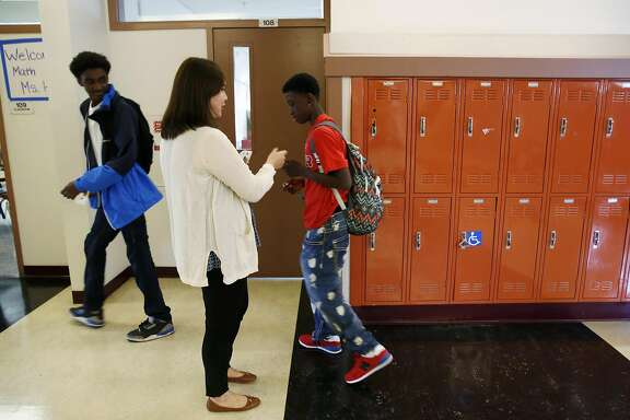Eighth grade math teacher Tina Hu hands out passes to students Damarion Travis (left) and Damani William on the first day of school at Martin Luther King Jr. Academic Middle School in San Francisco, California, on Monday, August 15, 2016.
