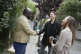 Kevin Adler (center), founder Miracle Messages, and Dennis Alexander (left)  shake hands as Jessica Day (right), director of programs Miracle Messages, looks on after Alexander recorded a video message  on Monday, August 15, 2016 in San Francisco, California.  Alexander said he has been homeless since 2012 and recorded a message to reconnect with his grandmother.