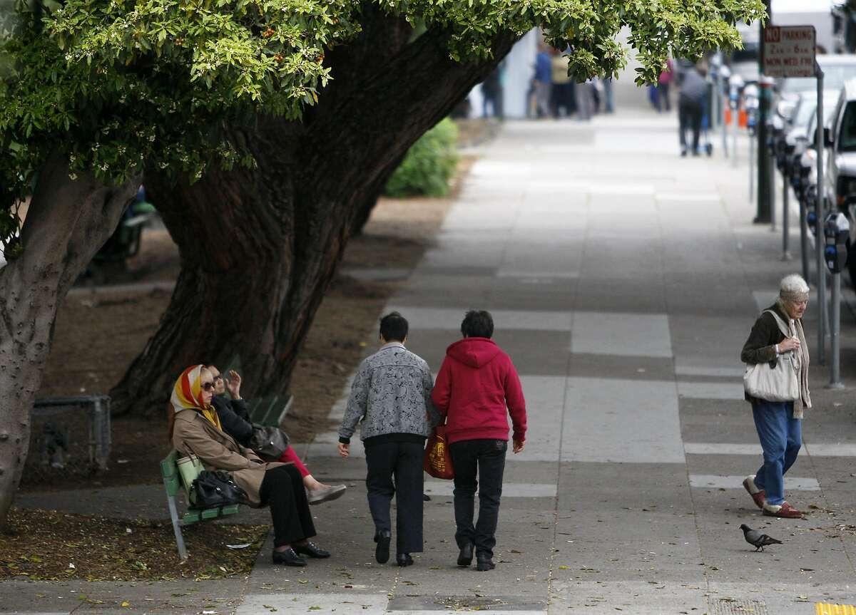 Pedestrians are seen on a sidewalk beside Washington Square Park in San Francisco's North Beach neighborhood.