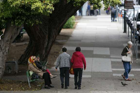 Pedestrians are seen on a sidewalk beside Washington Square Park in San Francisco's North Beach neighborhood on Thursday, Feb. 19, 2015.