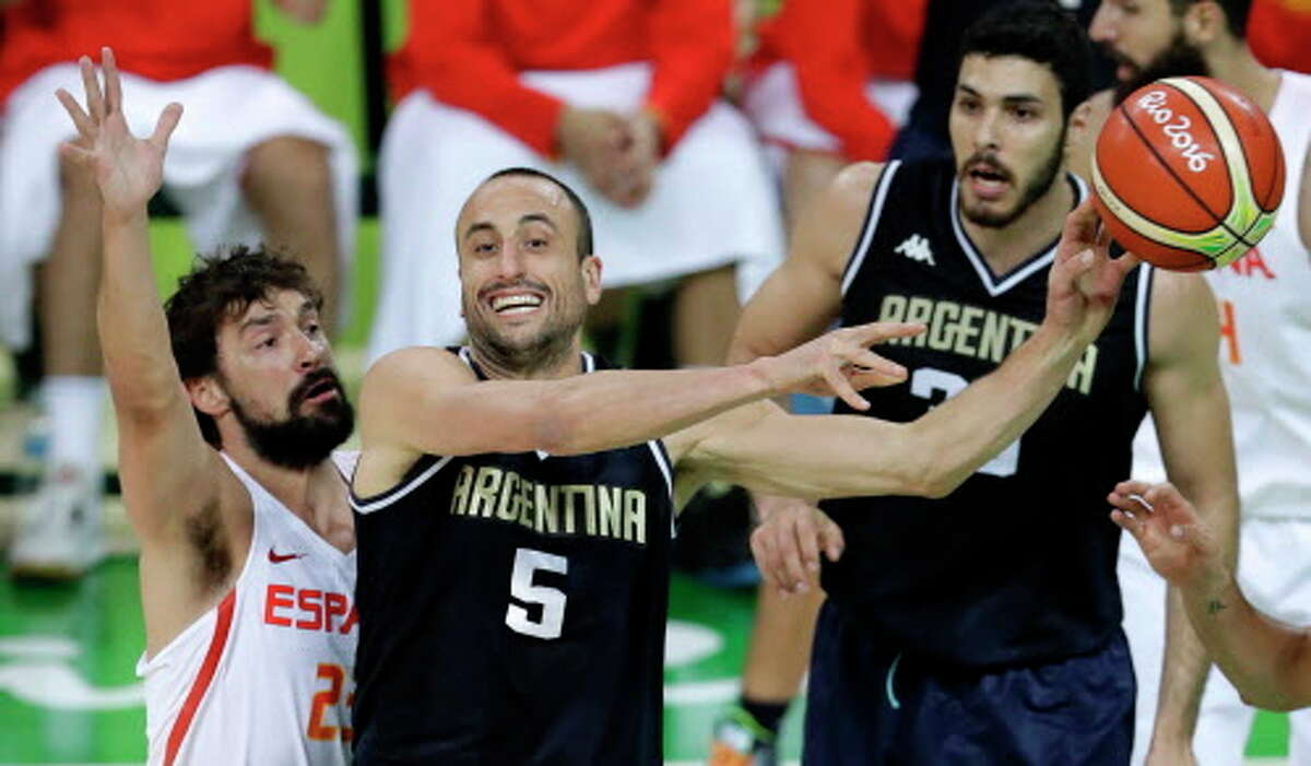 Argentina's Manu Ginobili (5) passes in front of Spain's Sergio Llull, left, during a basketball game at the 2016 Summer Olympics in Rio de Janeiro, Brazil, Monday, Aug. 15, 2016. (AP Photo/Charlie Neibergall)