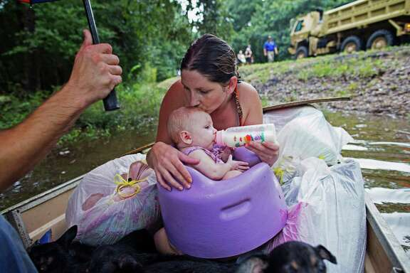 Danielle Blount kisses her 3-month-old baby Ember as she feeds her while they wait to be evacuated by members of the Louisiana Army National Guard near Walker, La., after heavy rains inundating the region, Sunday, Aug. 14, 2016.