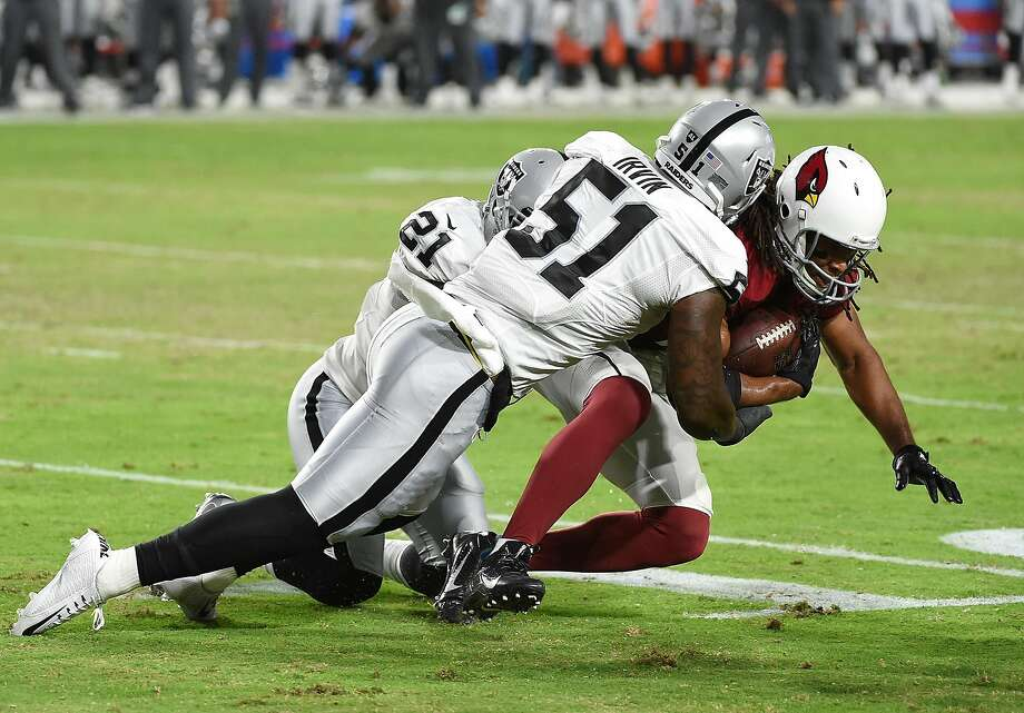 GLENDALE, AZ - AUGUST 12:  Bruce Irvin #51 and Sean Smith #21 of the Oakland Raiders make a tackle on Larry Fitzgerald #11 of the Arizona Cardinals during the first half at University of Phoenix Stadium on August 12, 2016 in Glendale, Arizona.  (Photo by Norm Hall/Getty Images) Photo: Norm Hall, Getty Images