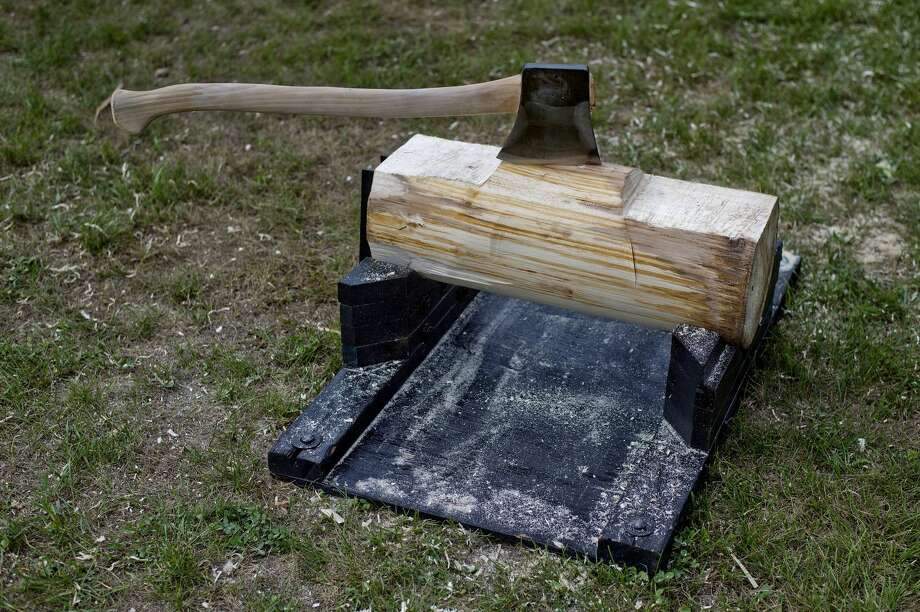 An axe and log are on display before the start of the Great Lakes Timber Show on Monday at the Midland County Fairgrounds. The show, which runs three times a day, features various wood-cutting demonstrations, axe throwing and floating log rolling games. Photo: NICK KING   Nking@mdn.net
