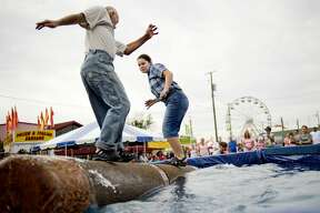 Emily Saari, right, and her father Robert battle to stay on a floating log the longest during a log rolling game during the Great Lakes Timber Show on Monday at the Midland County Fairgrounds. The show, which runs three times a day, features various wood-cutting demonstrations, axe throwing and floating log rolling games.
