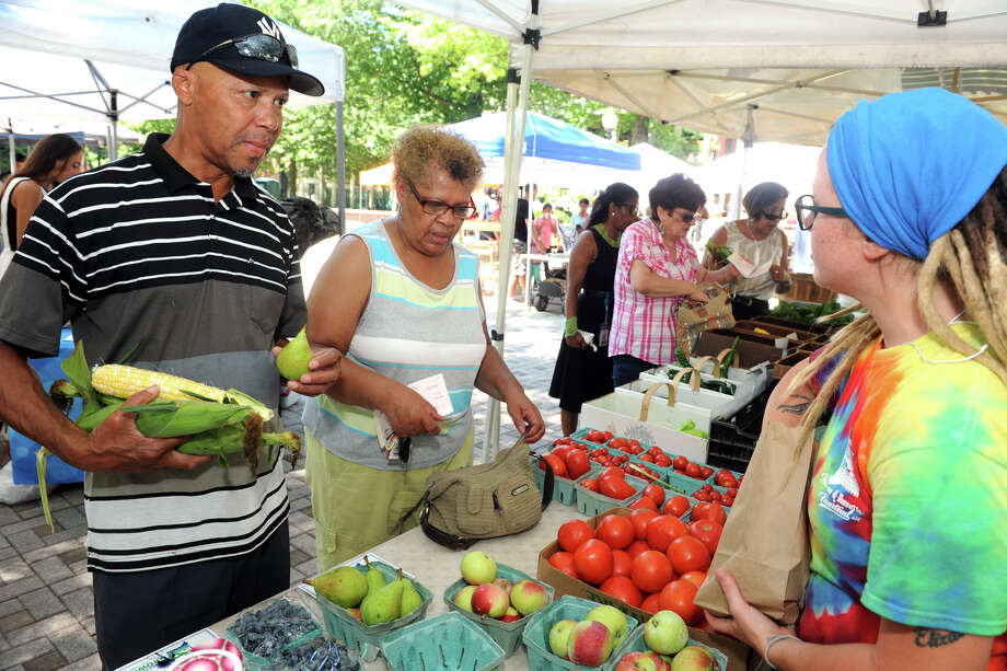 Calvin Washington, left, of Bridgeport, buys corn and fruit from Amanda Hill, right, from Killam & Bassette Farmstead in South Glastonbury, at the Farmer's Market in McLevy Square in Bridgeport. The market is open every Thursday afternoon. Photo: Ned Gerard / Hearst Connecticut Media / Connecticut Post
