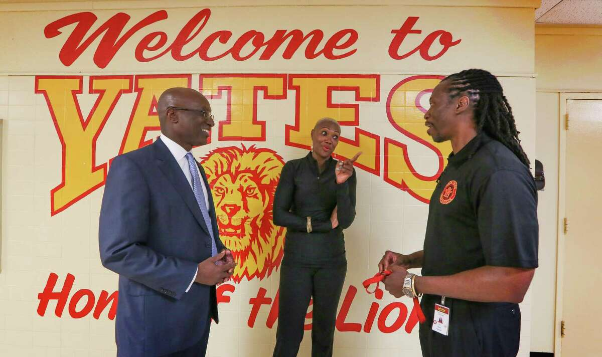 Ken Huewitt, then the interim superintendent of HISD, left, and trustee Jolanda Jones congratulated Yates High School Principal Kenneth Davis in August 2016. The school had come off the state's low-performing list.
