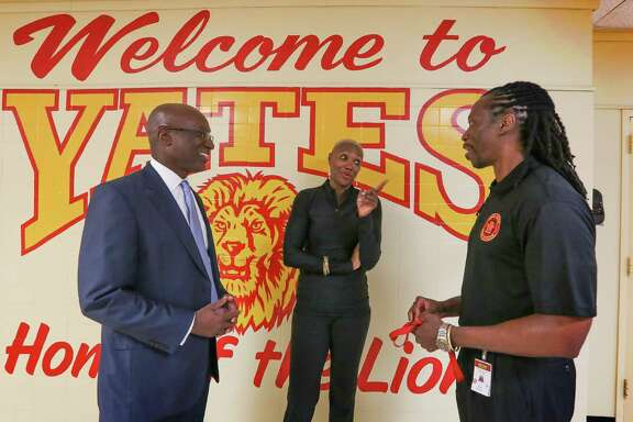 "Kenneth ""Ken"" Huewitt, interim superintendent of HISD, left, and trustee Jolanda Jones congratulate Principal Kenneth Davis on Monday. His campus, Jack Yates, met the state's standards."