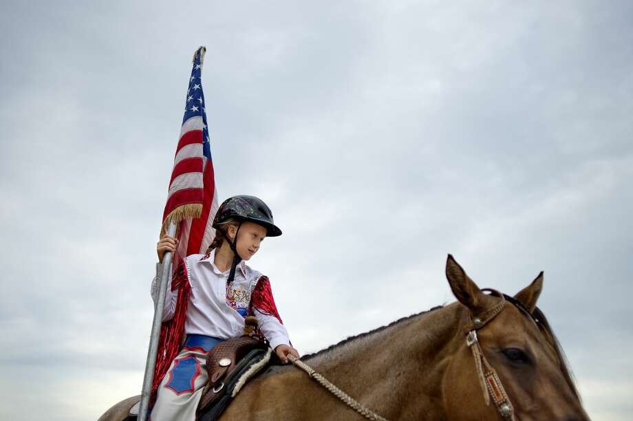 Isabel Cumper, 9, of Freeland, sits on her horse Jazz before carrying the flag in the opening ceremony during the Super Kicker Rodeo on Monday at the Midland County Fairgrounds. Crumper and her mother compete in the barrel racing event. Photo: NICK KING | Nking@mdn.net