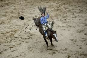 Cody Conklin rides the horse Cat Scratch Fever while participating in the bareback riding event during the Super Kicker Rodeo on Monday at the Midland County Fairgrounds.