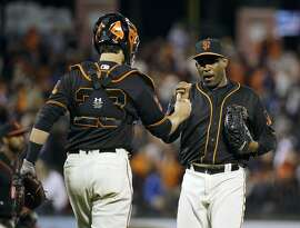 San Francisco Giants relief pitcher Santiago Casilla, right, is greeted by catcher Buster Posey, left, after a baseball game against the Baltimore Orioles, Saturday, Aug. 13, 2016, in San Francisco. San Francisco won the game 6-2. (AP Photo/Eric Risberg)