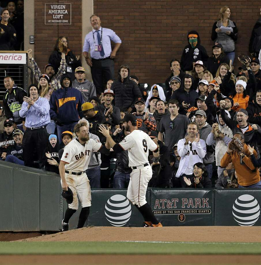Fans and first baseman Brandon Belt show appreciation for Hunter Pence (left), who made a catch Monday after falling. Photo: Carlos Avila Gonzalez, The Chronicle