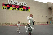 metro daily - Gabriela Garcia , right, walks with her son Nathaniel Garcia, away from the Montgomery Wards store at Windsor Park Mall, Mar. 24, 2001, where she found a broken chair for $10.00, that matches her chairs at home. photo Bob owen