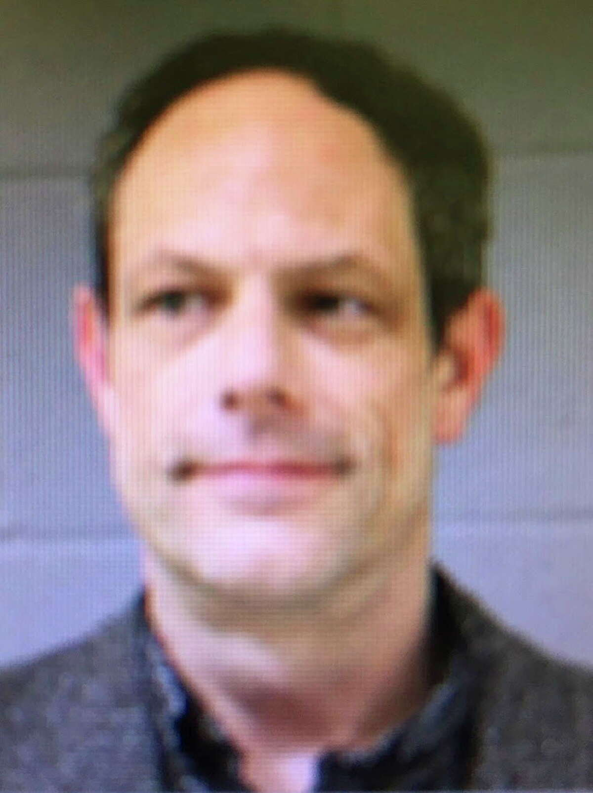 FILE - This booking photo released by the Newtown Police Department shows Jason Adams, arrested Wednesday, April 6, 2016, and charged with having a gun at the town's middle school. Adams, 46, a teacher at the school, was charged with possession of a weapon on school grounds, which is illegal in Connecticut. Newtown School Superintendent Joseph Erardi confirmed Saturday, July 2, that Adams resigned at the end of the school year. (Newtown Police Department via AP)