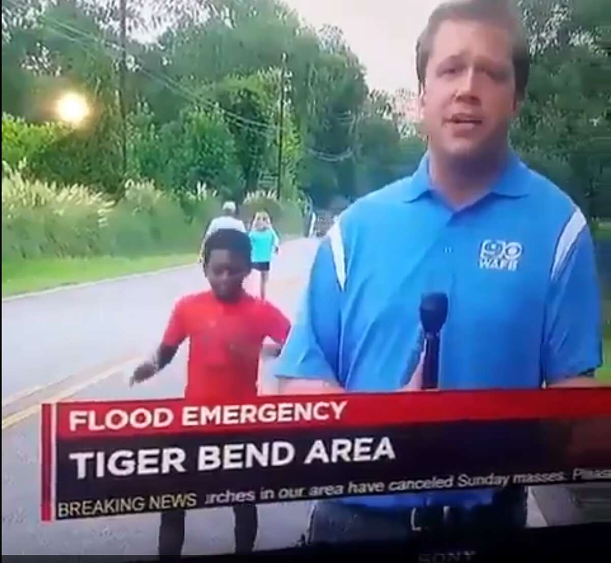 A young boy danced behind a news reporter from WAFB, a CBS-affiliate in Baton Rouge, during a broadcast Aug. 14, 2016.