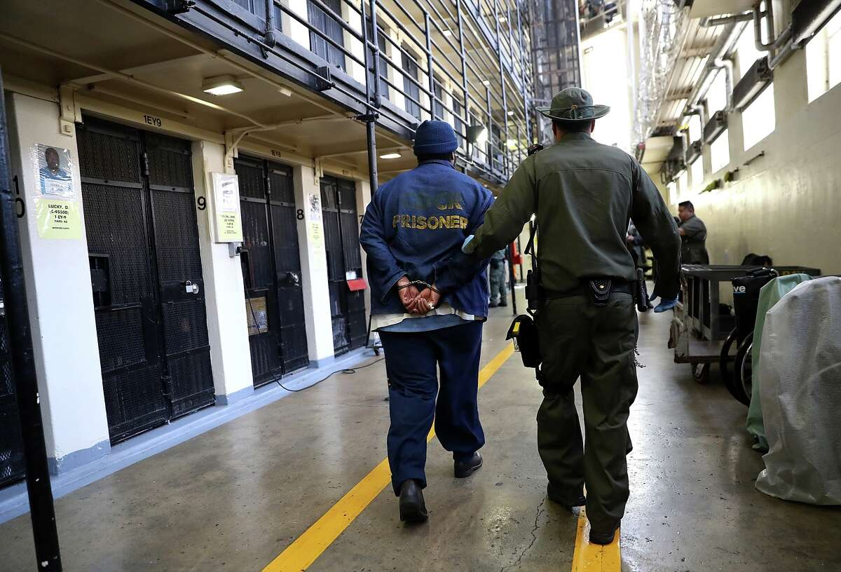 An armed California Department of Corrections and Rehabilitation (CDCR) officer escorts a condemned inmate at San Quentin State Prison.