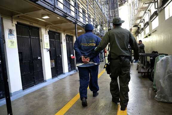 An armed California Department of Corrections and Rehabilitation (CDCR) officer escorts a condemned inmate at San Quentin State Prison's death row on August 15, 2016 in San Quentin, California.  San Quentin State Prison opened in 1852 and is California's oldest penitentiary. The facility houses the state's only death row for men that currently has 700 condemned inmates.  (Photo by Justin Sullivan/Getty Images)