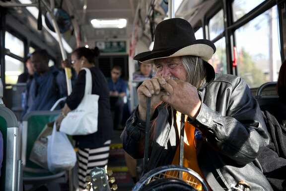 Sam Stone rides a bus to play mandolin at an open mic in Alameda, Calif. on Wednesday, August 3, 2016. Stone has been homeless here on and off since 2007.