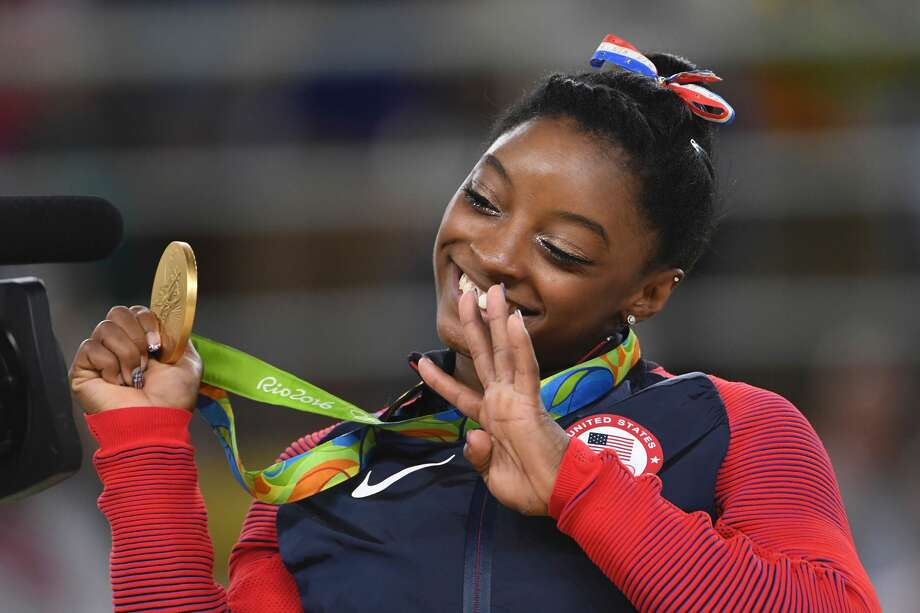 US gymnast Simone Biles celebrates on the podium of the women's floor event final of the Artistic Gymnastics at the Olympic Arena during the Rio 2016 Olympic Games in Rio de Janeiro on August 16, 2016. / AFP / Toshifumi KITAMURA        (Photo credit should read TOSHIFUMI KITAMURA/AFP/Getty Images) Photo: TOSHIFUMI KITAMURA/AFP/Getty Images