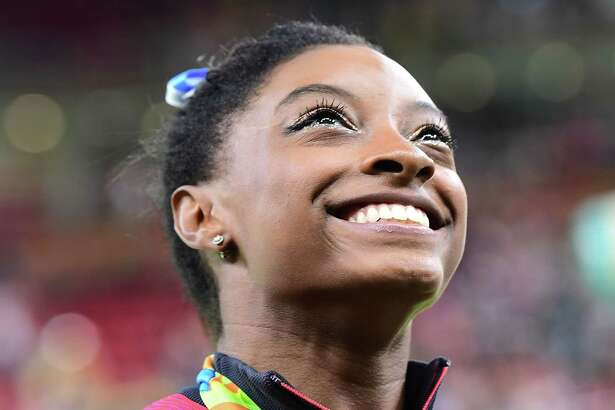 Simone Biles was all smiles as she made gymnastics history with an easy victory in the all-around competition.