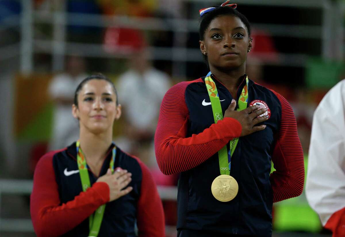 From left, United States' Aly Raisman, silver for floor, and compatriot Simone Biles stand for their national anthem during the artistic gymnastics women's apparatus final at the 2016 Summer Olympics in Rio de Janeiro, Brazil, Tuesday, Aug. 16, 2016. (AP Photo/Rebecca Blackwell)