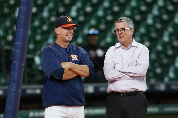 Houston Astros manager A.J. Hinch chats with GM Jeff Luhnow during batting practice before the start of an MLB game at Minute Maid Park,Tuesday, Aug. 16, 2016, in Houston.