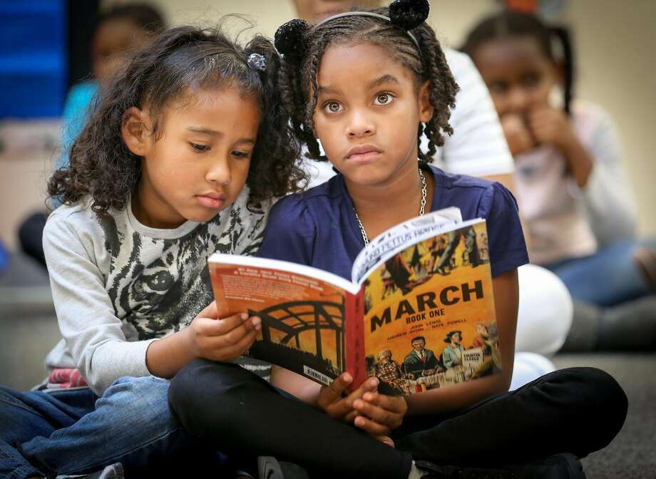 "Students Isabella (left) and Talaya, both 6, follow along during a reading of the graphic paperback ""March"" by Rep. John Lewis at the Ella Hill Hutch Community Center in the Western Addition. Photo: Amy Osborne, Special To The Chronicle"