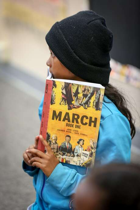 "Katlin, 10, holds a copy of John Lewis' ""March: Book One"" during the reading at the Ella Hill Hutch Community Center. Photo: Amy Osborne, Special To The Chronicle"