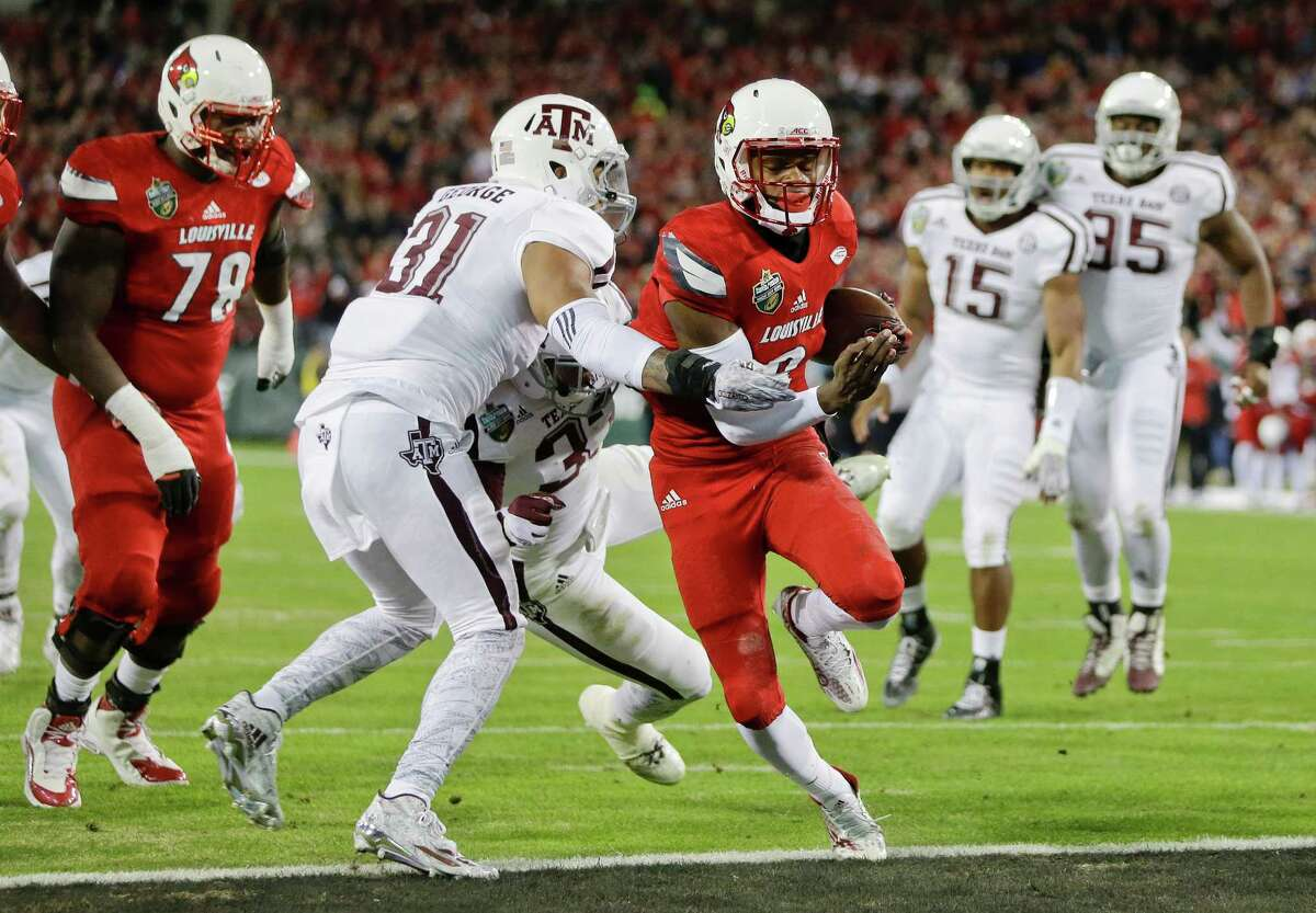 Louisville quarterback Lamar Jackson (8) gets past Texas A&M defenders Claude George (31) and Shaan Washington (33) to score a touchdown on a 6-yard run in the first half of the Music City Bowl on Dec. 30, 2015, in Nashville, Tenn.