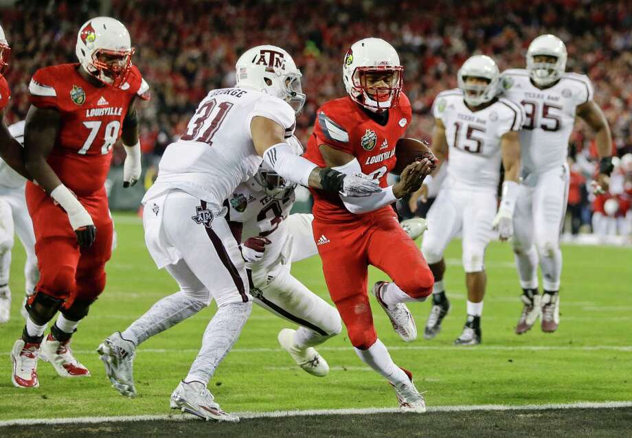 Louisville quarterback Lamar Jackson (8) gets past Texas A&M defenders Claude George (31) and Shaan Washington (33) to score a touchdown on a 6-yard run in the first half of the Music City Bowl on Dec. 30, 2015, in Nashville, Tenn. Photo: Mark Humphrey /Associated Press / AP