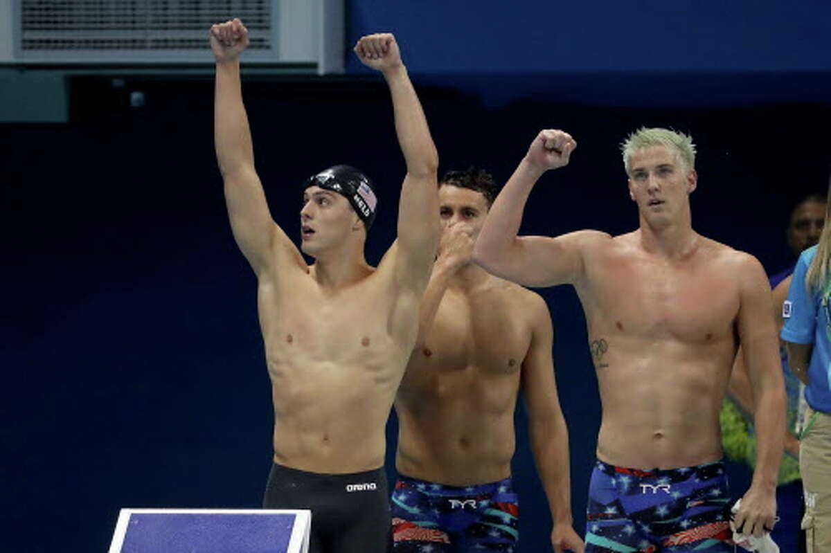 RIO DE JANEIRO, BRAZIL - AUGUST 07: James Feigen, Ryan Held and Blake Pieroni of the United States celebrate winning heat two of the Men's 4 x 100m Freestyle Relay on Day 2 of the Rio 2016 Olympic Games at the Olympic Aquatics Stadium on August 7, 2016 in Rio de Janeiro, Brazil. (Photo by Al Bello/Getty Images)