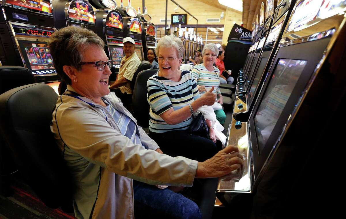 """Trinity, Texas resident Shirley Sheffield (center) reacts as Patti Rau (left) wins on a gaming machine as their friend Jan Pistole watches on at Naskila Entertainment in Livingston, Texas on Tuesday, June 7, 2016.The Alabama Coushatta Indian Tribe in Livingston - about an hour north of Houston - reopened its casino after a 14-year closure prompted by threats from the state of Texas to take legal action against the tribe. Recent legal developments paved the way for the reopening. With 365 Class 2 electronic gaming devices, the former casino has been renamed Naskila Entertainment and its doors opened earlier this month to eager guests and gamers. Only """"bingo"""" type machines are in use at Naskila Entertainment according to officials. (Kin Man Hui/San Antonio Express-News)"""