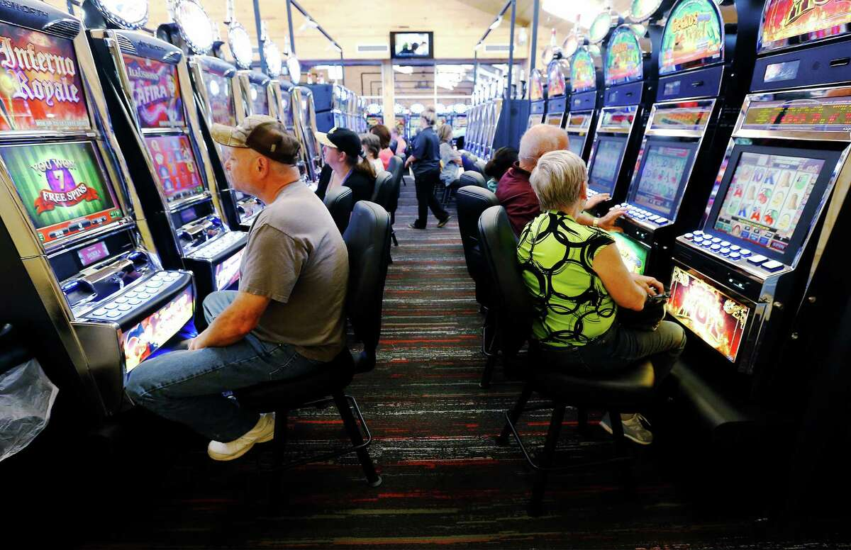 """Gamers occupy a row of machines at Naskila Entertainment in Livingston, Texas on Tuesday, June 7, 2016. The Alabama Coushatta Indian Tribe in Livingston - about an hour north of Houston - reopened its casino after a 14-year closure prompted by threats from the state of Texas to take legal action against the tribe. Recent legal developments paved the way for the reopening. With 365 Class 2 electronic gaming devices, the former casino has been renamed Naskila Entertainment and its doors opened earlier this month to eager guests and gamers. Only """"bingo"""" type machines are in use at Naskila Entertainment according to officials. (Kin Man Hui/San Antonio Express-News)"""