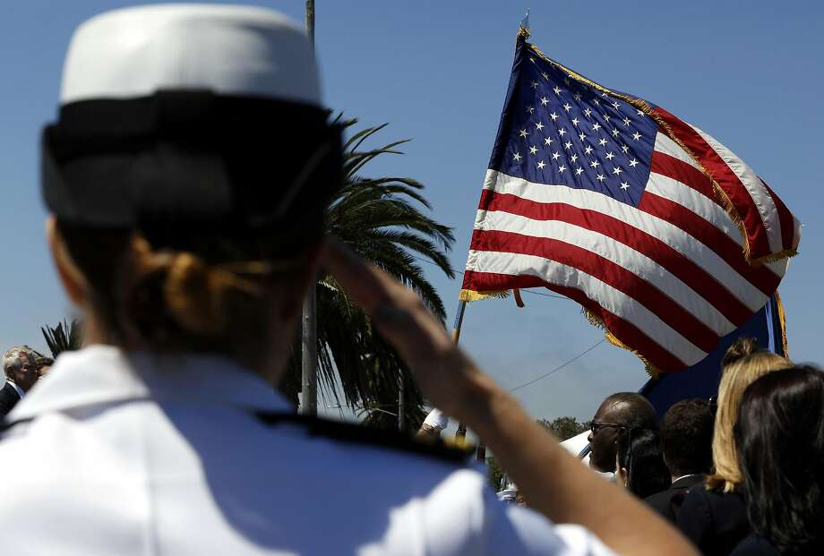 A Navy sailor salutes the American flag during the presentation of colors at the naming ceremony for the USNS fleet oiler Harvey Milk at Treasure Island, California, on Tuesday, August 16, 2016. Photo: Connor Radnovich, The Chronicle