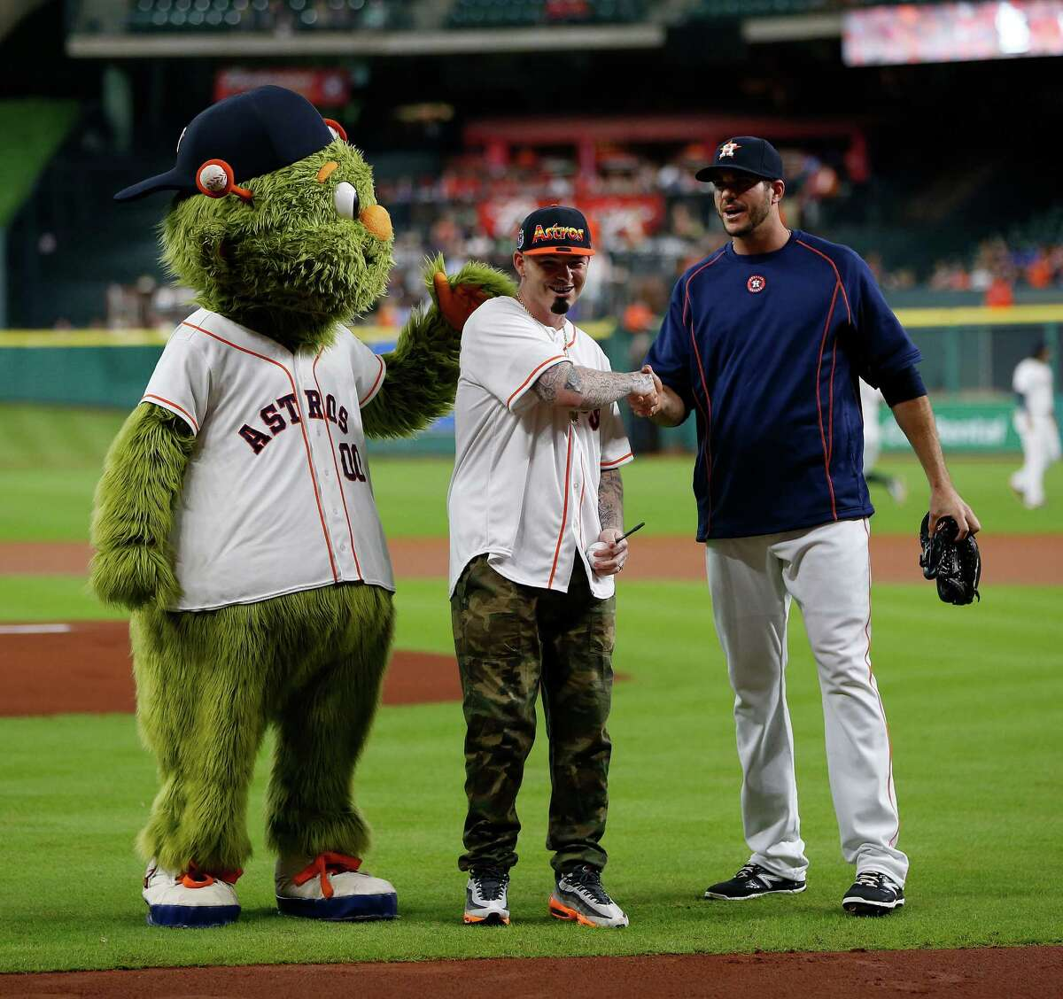 Rapper Paul Wall with Orbit and Houston Astros relief pitcher James Hoyt (51) after throwing out the first pitch before the start of an MLB game at Minute Maid Park,Tuesday, Aug. 16, 2016, in Houston.