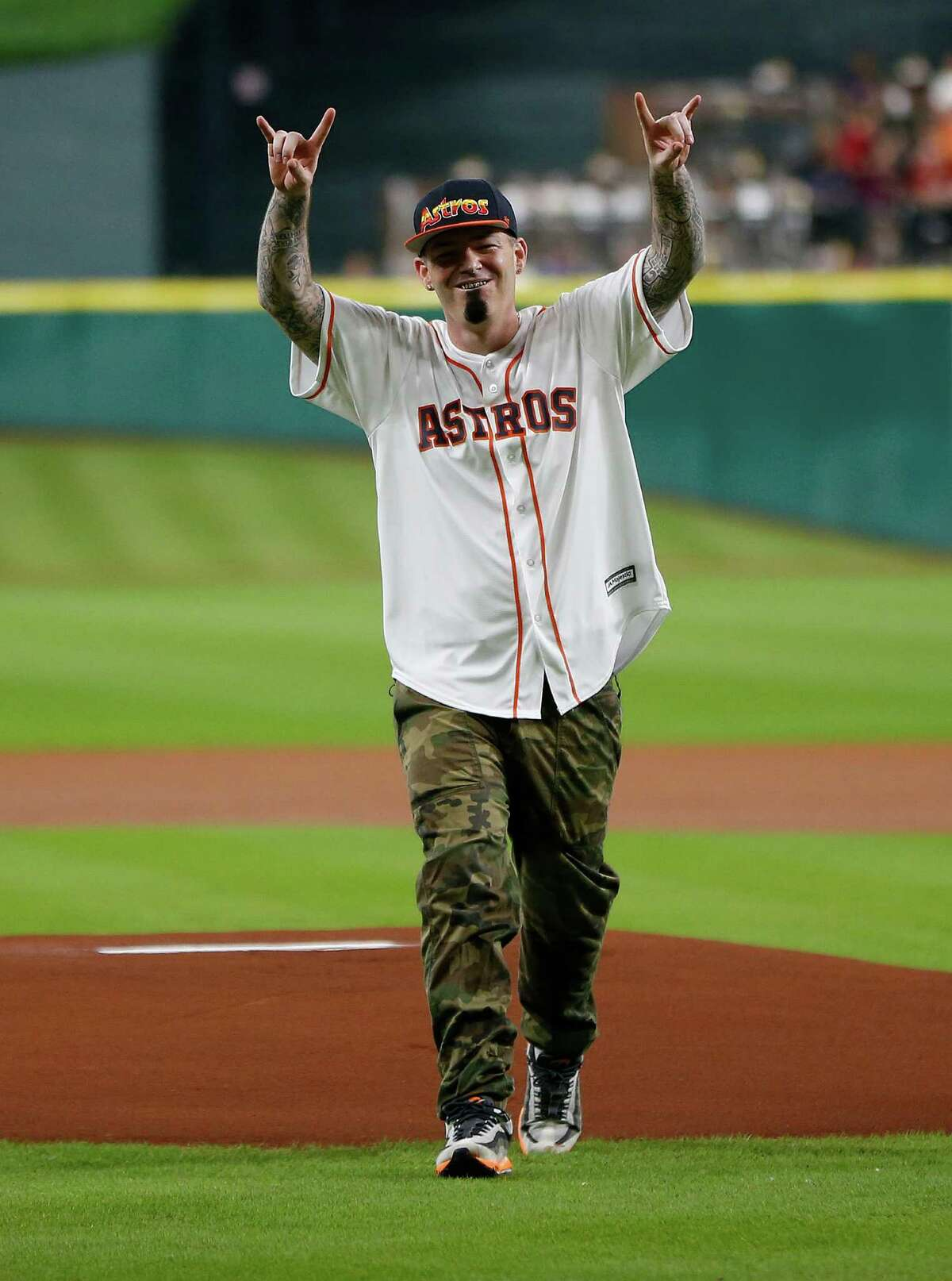Rapper Paul Wall reacts after throwing out the first pitch before the start of an MLB game at Minute Maid Park,Tuesday, Aug. 16, 2016, in Houston.