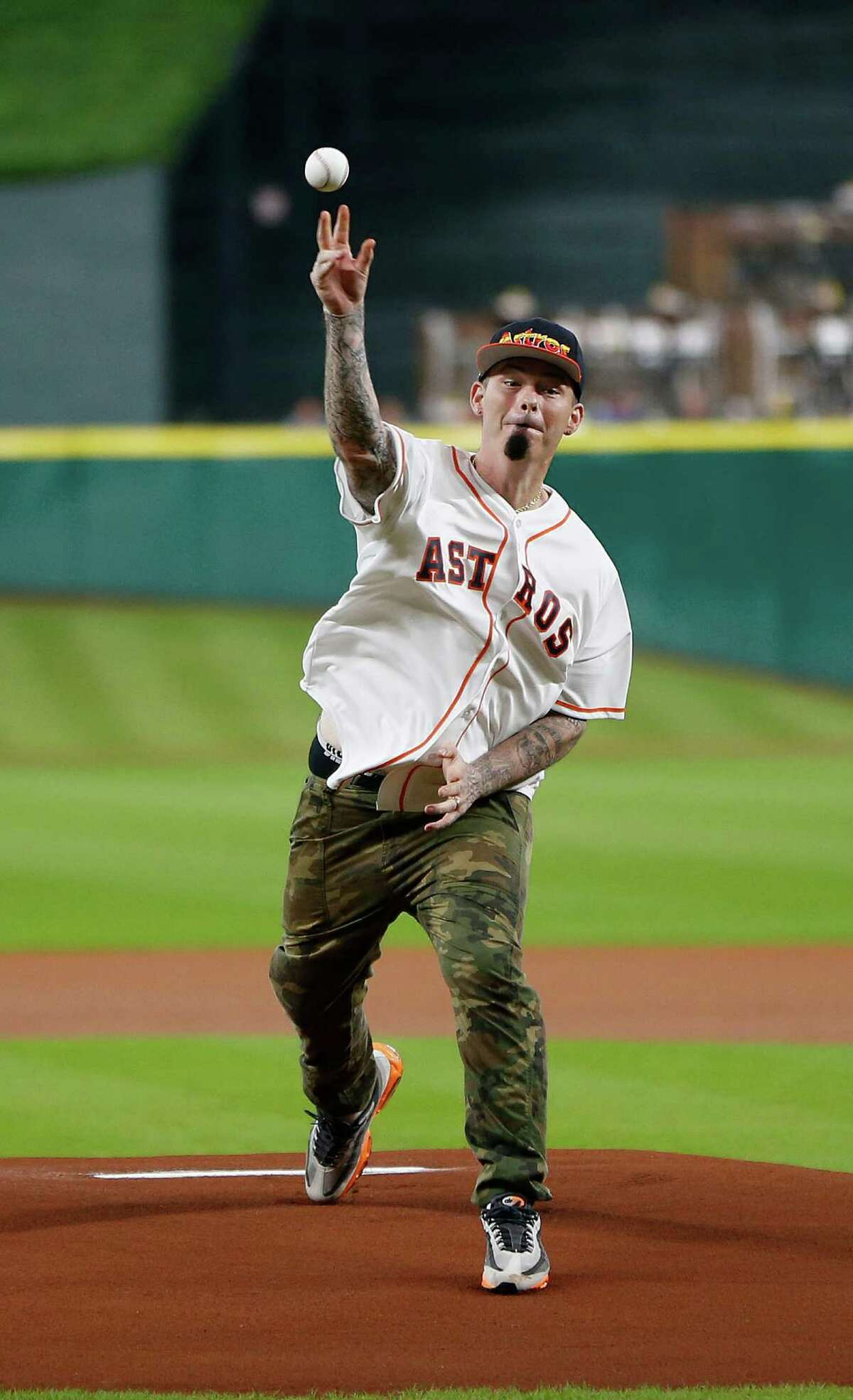 Rapper Paul Wall throws out the first pitch before the start of an MLB game at Minute Maid Park,Tuesday, Aug. 16, 2016, in Houston.