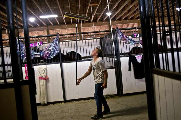 Glendale, Ariz. resident Michael Fisher, 12, practices balancing a broom in one of the horse barns on Tuesday at the Midland County Fair. Fisher was visiting family during the fair and helped show his aunt's sheep.