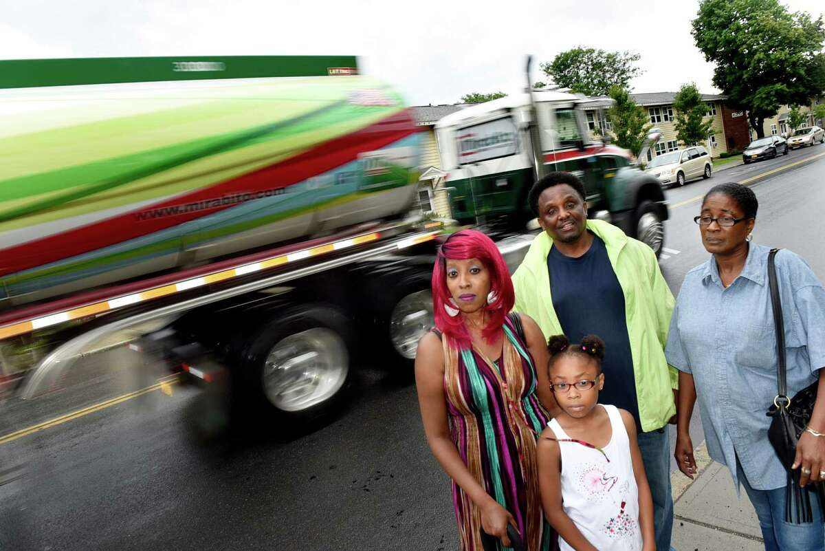 Residents Deneed Carter-El, left, her daughter Tatiyana Carter-El, 8, and Tammy Miller, right, join Brett Taylor, whose mother is a resident, on Tuesday, Aug. 16, 2016, at Ezra Prentice Homes in Albany, N.Y. They are all concerned about oil trains and heavy diesel tractor-trailer traffic. (Cindy Schultz / Times Union)