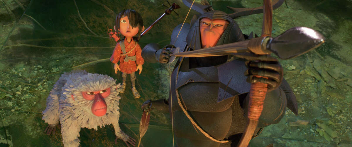 """This image released by Focus Features shows characters Monkey, voiced by Charlize Theron, left, Kubo, voiced by Art Parkinson, and Beetle, voiced by Matthew McConnaghey in a scene from the animated film, """"Kubo and the Two Strings."""" (Laika Studios/Focus Features via AP)"""