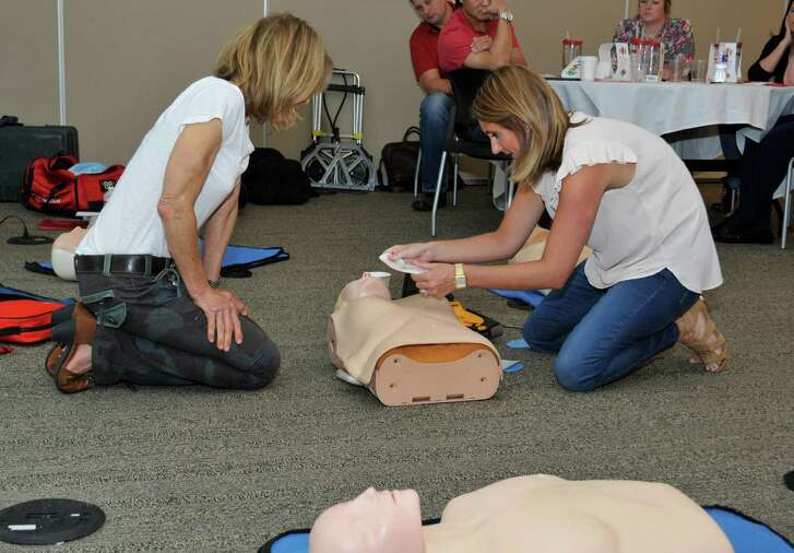Gail Gould with FITCORE, left, watches Quantas Service employee Aryn Guillory apply defibrillator pads during CPR training.
