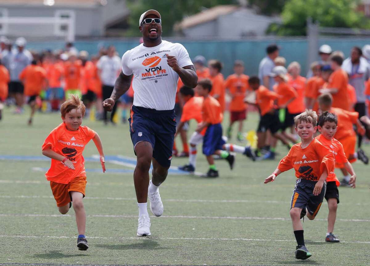 Denver Broncos linebacker Von Miller runs with participants, as the Super Bowl 50 MVP hosts a football camp for kids on a high school field, Wednesday, June 22, 2016, in Englewood, Colo. Miller is still mired in a contract stalemate with the Broncos. (AP Photo/David Zalubowski)